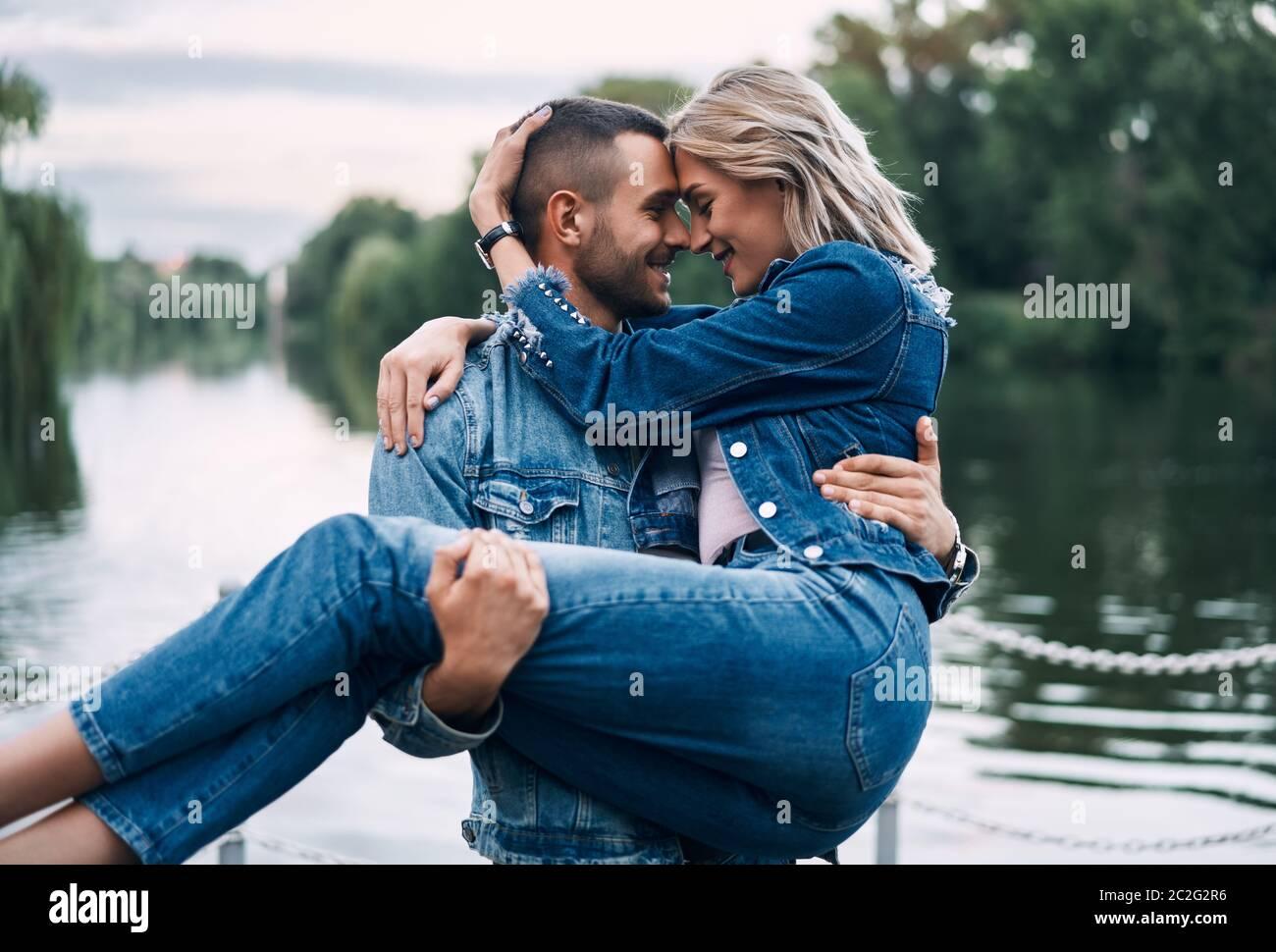 Feliz pareja disfrutar unos de otros en la naturaleza. Hombre sosteniendo a la mujer en las manos Foto de stock