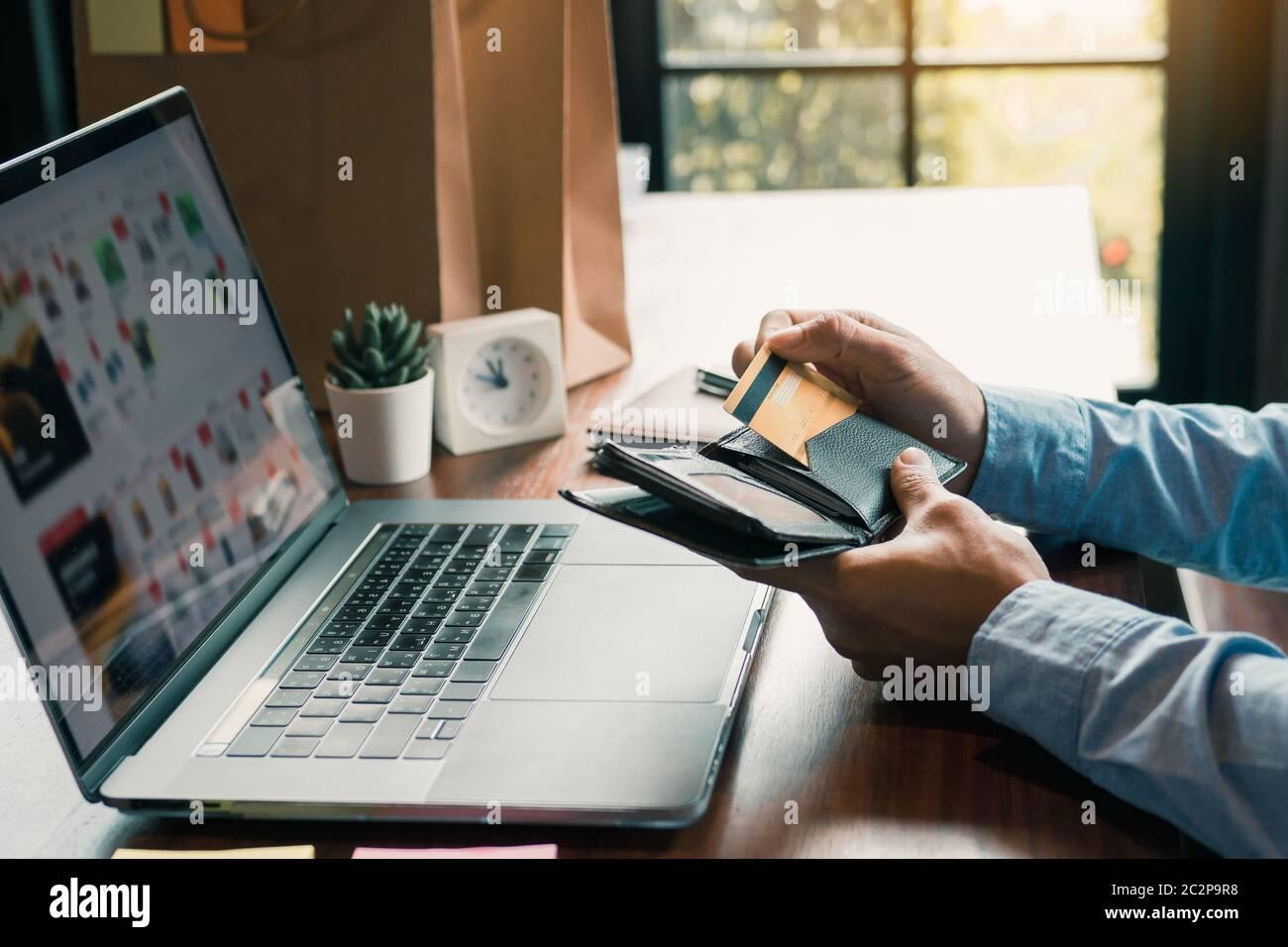 Mano de hombre asiático está sacando una tarjeta de crédito de su bolsillo para completar las compras en línea en el ordenador. Foto de stock