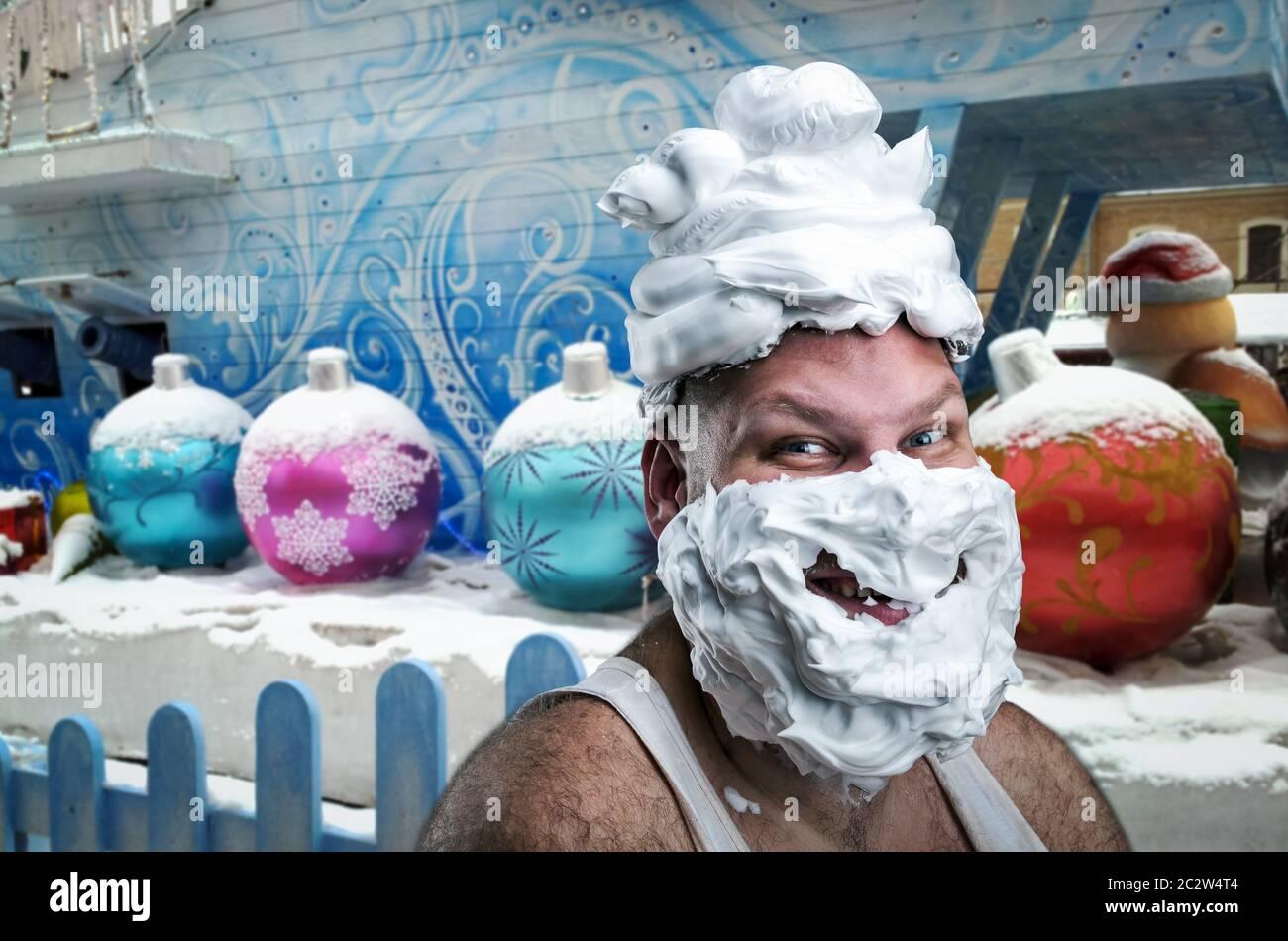 Extraño hombre sonriente con espuma de afeitar en su rostro y en su cabeza durante el invierno antecedentes Foto de stock