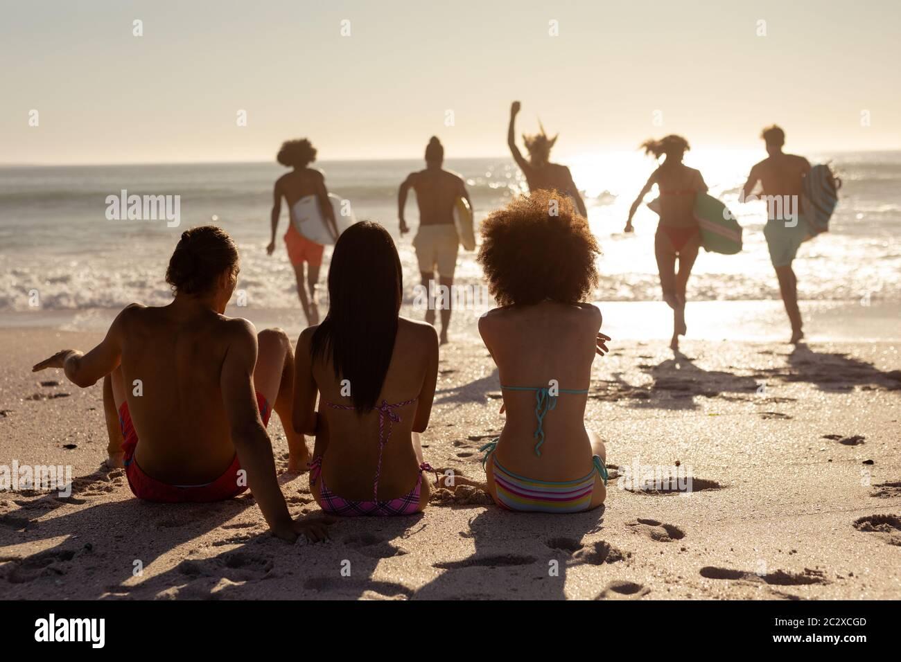 Grupo multiétnico de hombres y mujeres, surfing en la playa Foto de stock