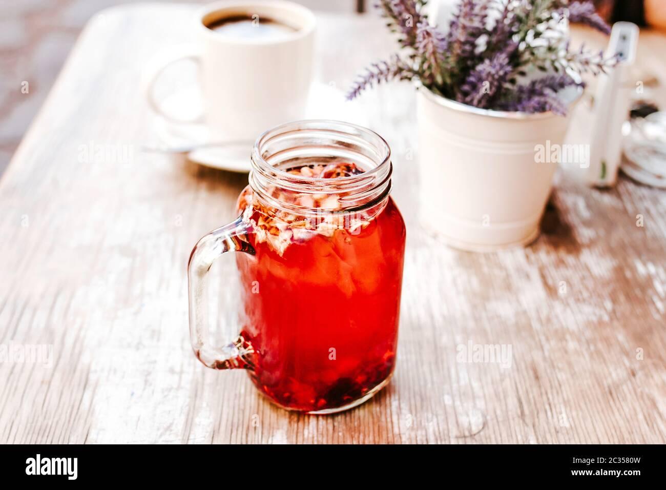 Tisana o té de hierbas rojas en un frasco transparente de cristal en una mesa al aire libre en una casa de té en la calle Foto de stock