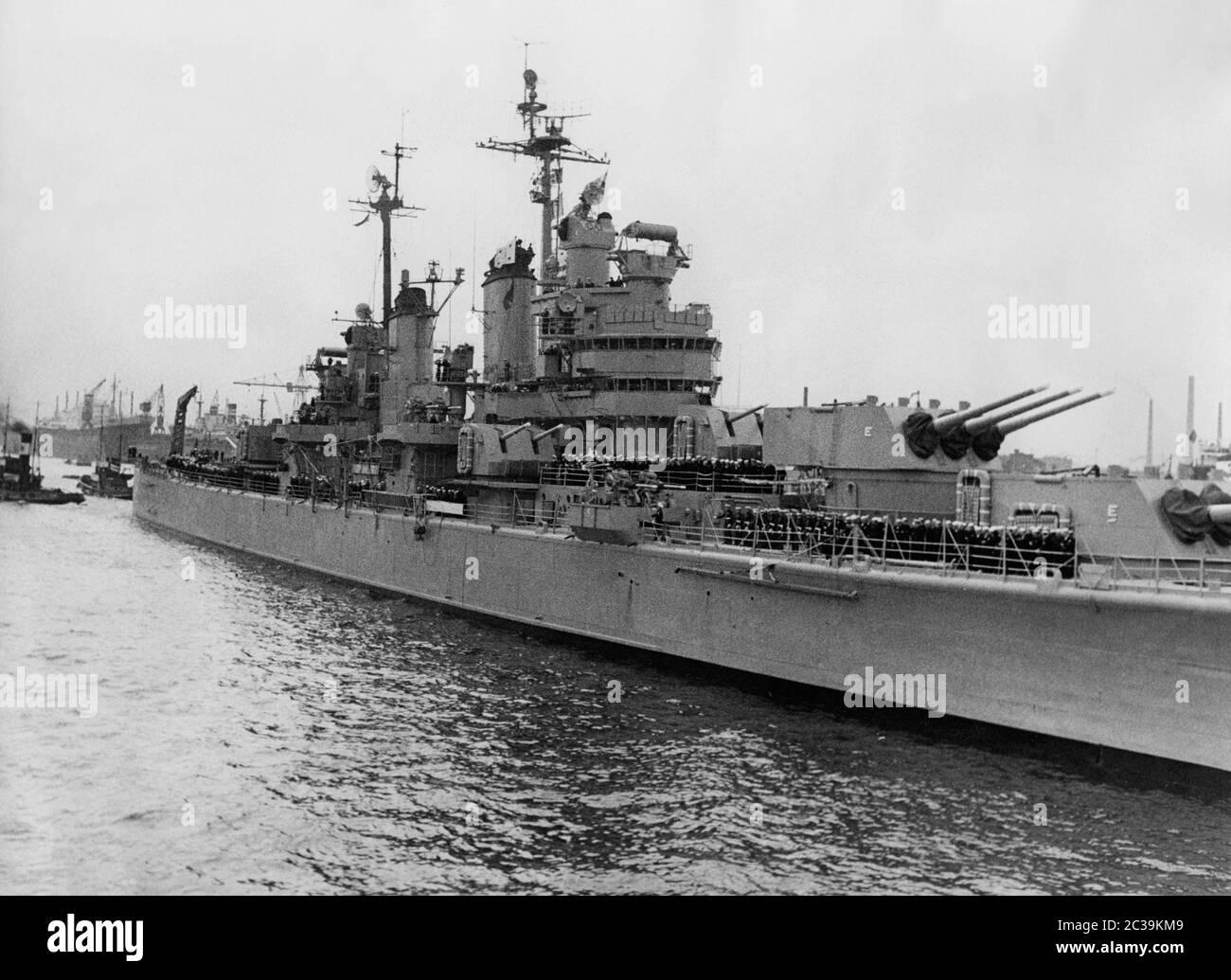 El USS Macon (crucero pesado de clase Baltimore) de la Marina de los EE.UU. Con la tripulación en cubierta durante una visita de la flota en Hamburgo en la década de 1950. Foto de stock