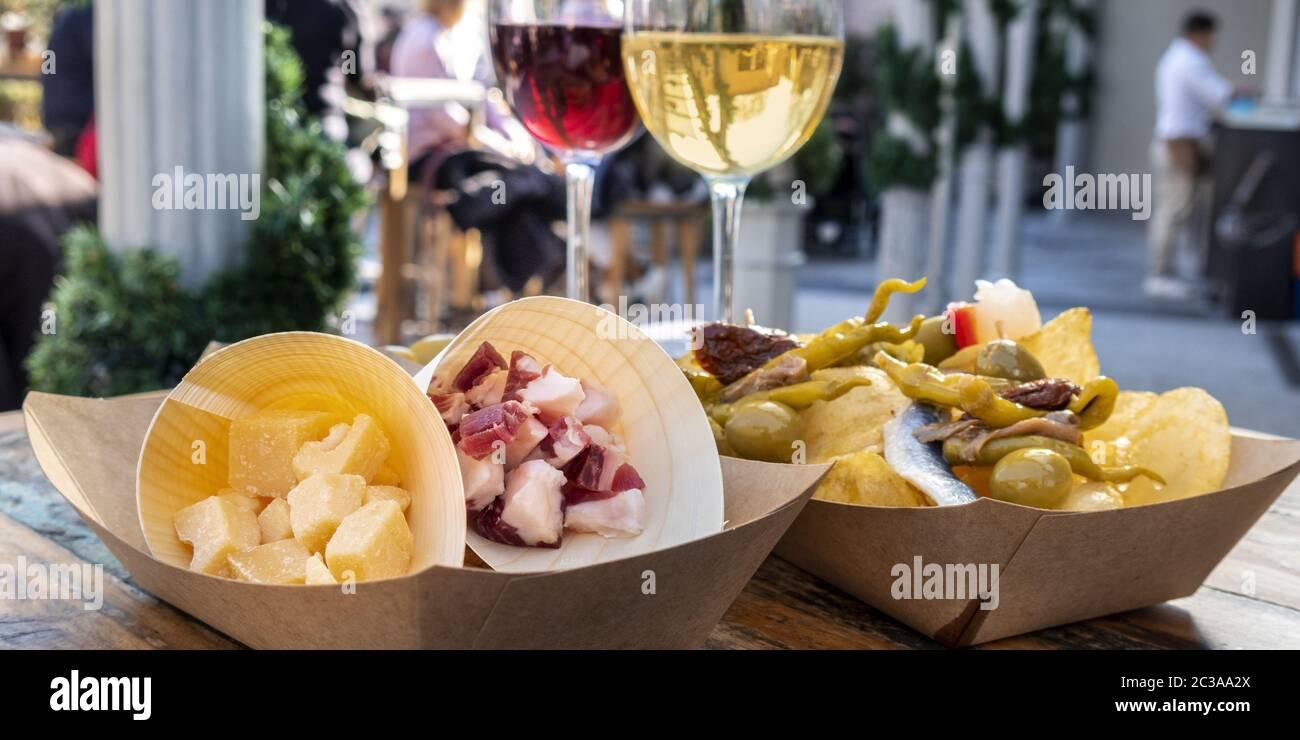 Panorama del bar de tapas. Queso, jamón y pinchos con vino tinto y blanco sobre una mesa de madera en una cafetería al aire libre Foto de stock