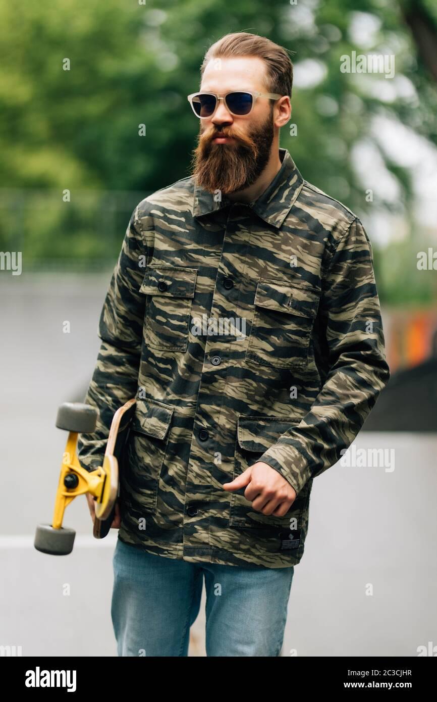 Hombre barbudo sosteniendo el longboard o el skateboard en el parque. Foto de stock
