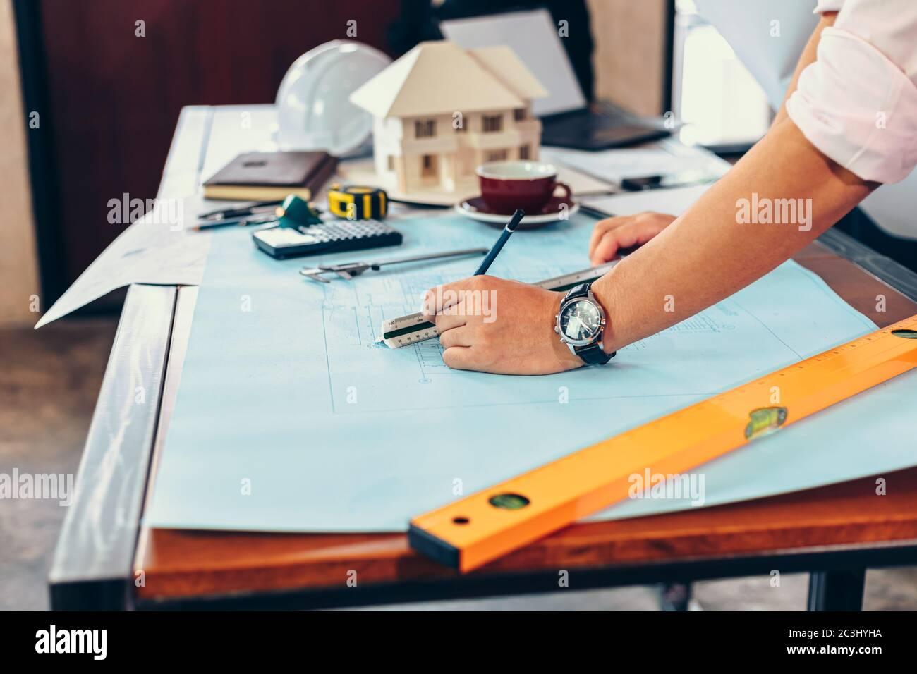 ingenieros que sostienen un bolígrafo que señala un edificio y el diseño de un plan de construcción de la instalación como guía para los constructores con detalles Foto de stock