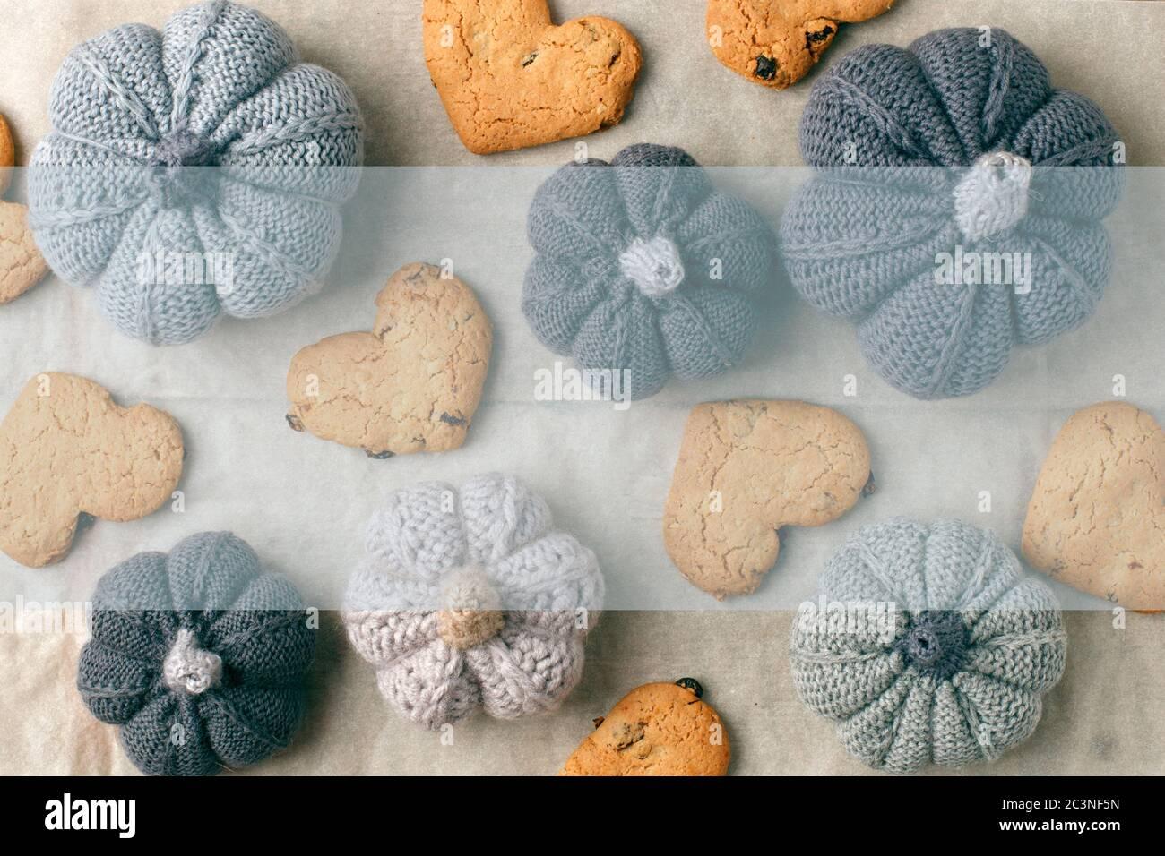 Otoño todavía la vida de la calabaza tejida hecha a mano, galletas en forma de corazón en papel de hornear. Concepto cálido hogar acogedor confort temporada otoño. Se burlan Foto de stock