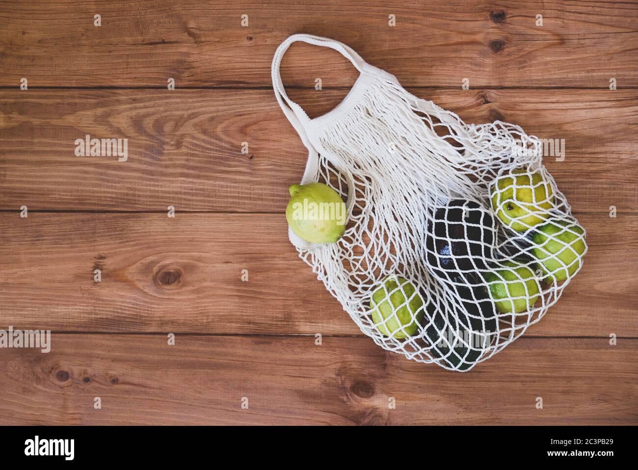Bolsa de malla de algodón reutilizable ecológica con limones y aguacate sobre fondo rústico de madera. Foto de stock