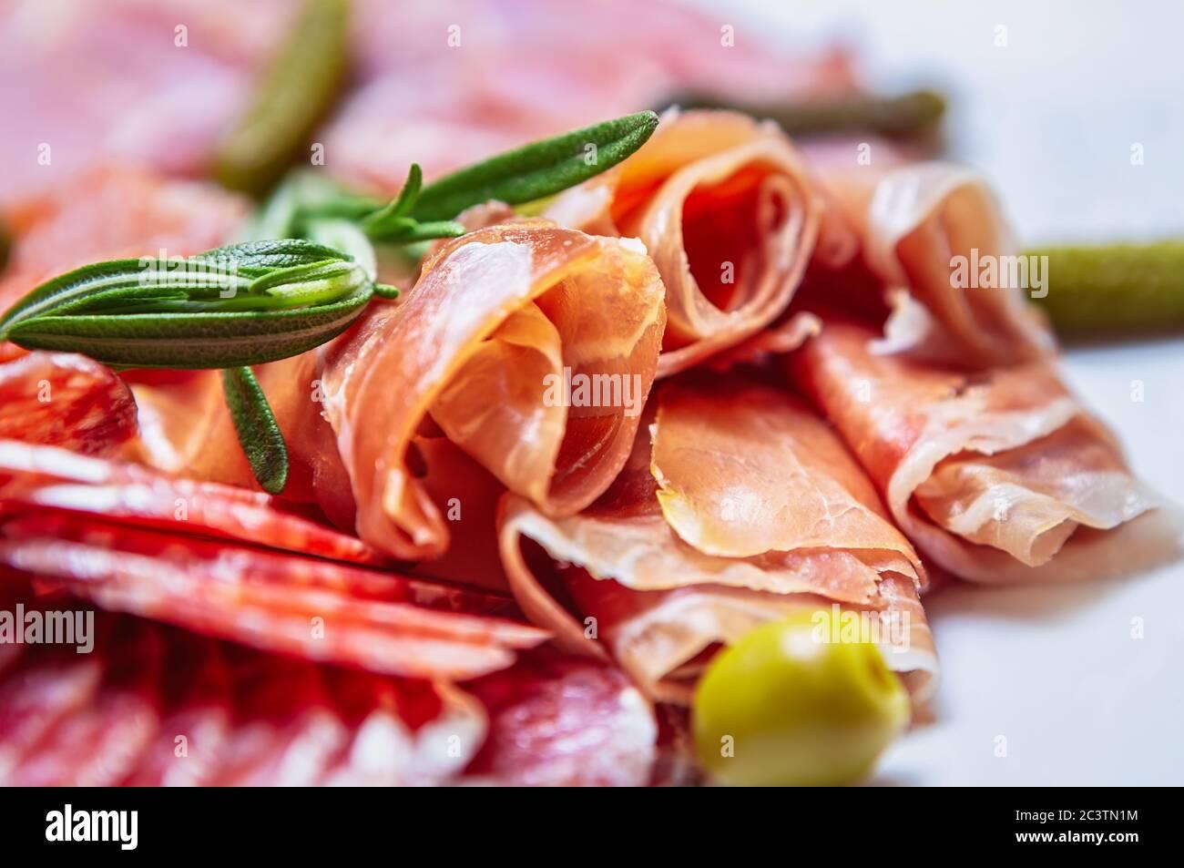 Deliciosos aperitivos de carne para la cena. Jamón español en rebanadas, salchichas de pepperoni, jamón de ternera servido en el plato del restaurante para aperitivos. Gourmet comida mediterránea f Foto de stock