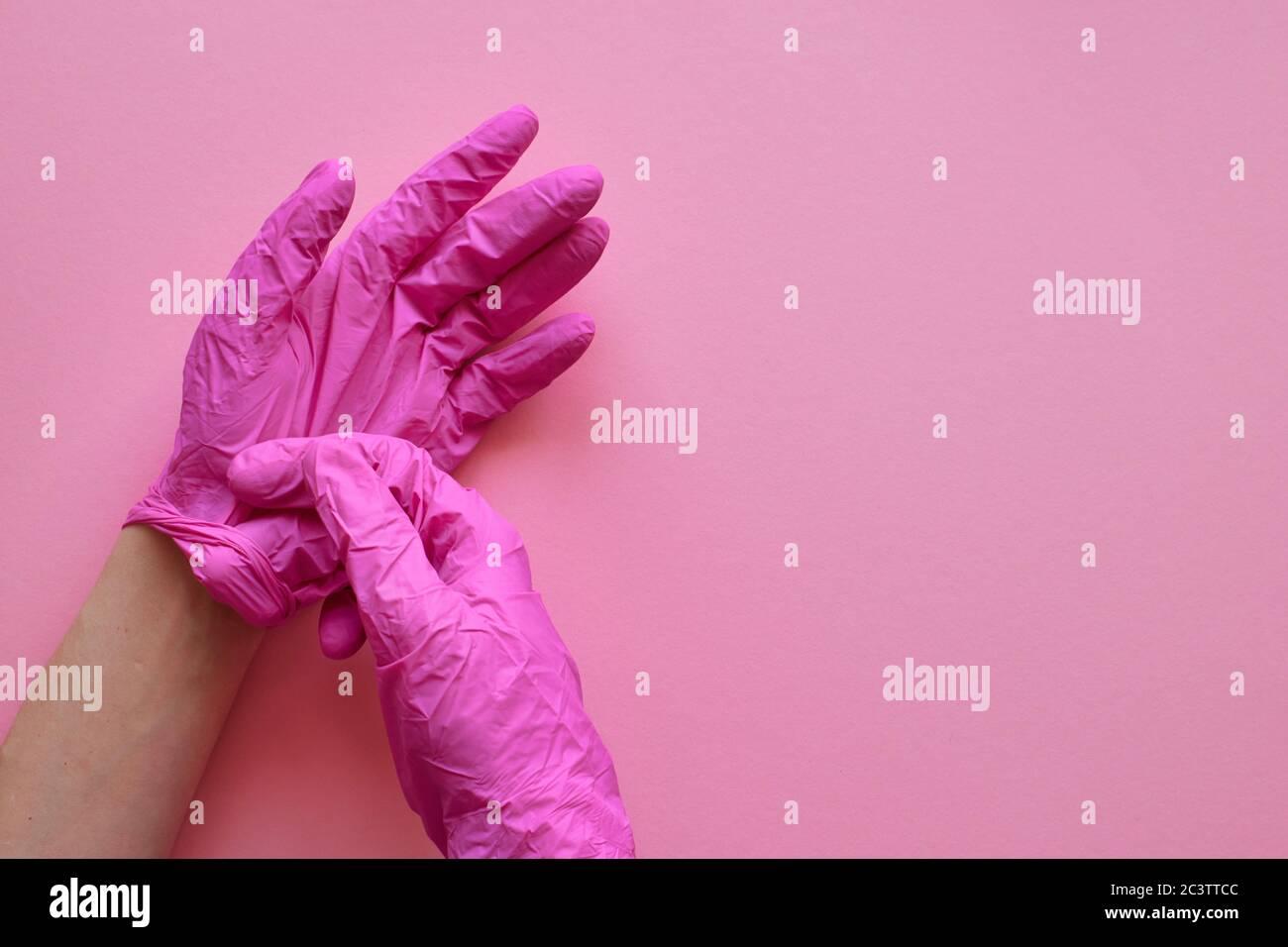 Manos con guantes rosas sobre fondo rosa. Concepto de prevención del virus coronavirus covid-19. Fondo rosa, copyspase. Diseño, vista superior, plano. Foto de stock