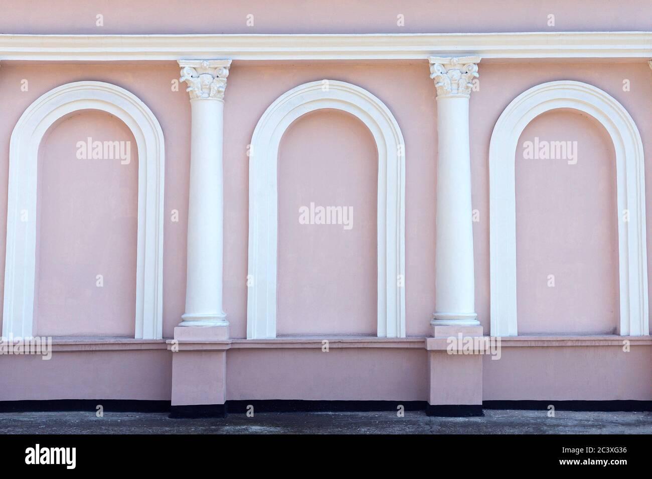 Fachada rosa sin ventanas del edificio con columnas blancas y arcos. Hermoso exterior. Fondo, fondo de pantalla Foto de stock