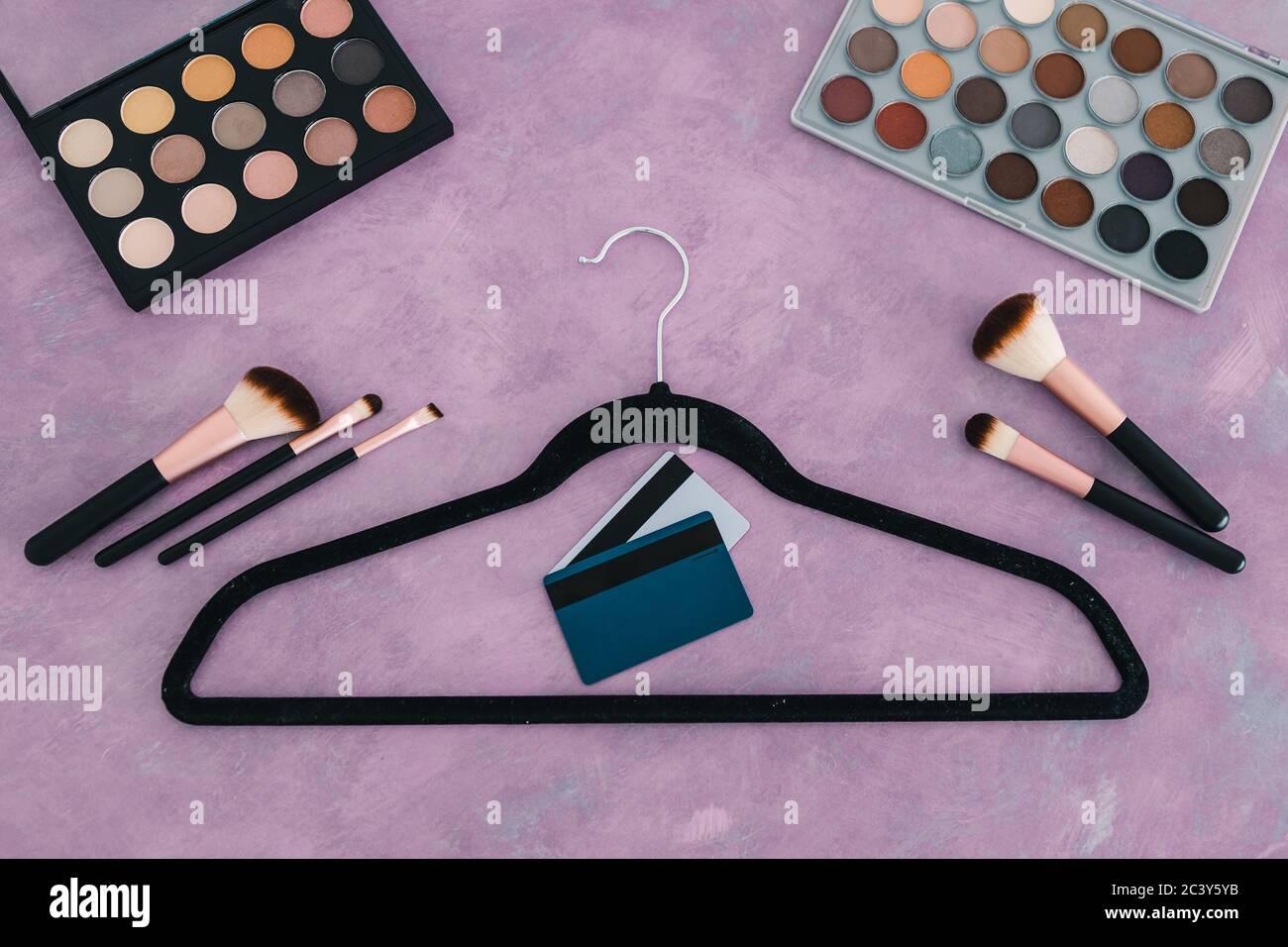 industria de la belleza y concepto de compras, escritorio rosa con cosméticos y accesorios de moda en ella, incluyendo percha de ropa y tarjetas de crédito Foto de stock