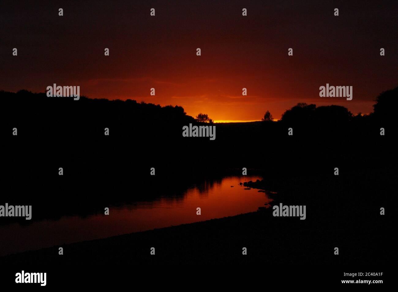 Secuencia de imágenes de una puesta de sol, pantano de Swinsty en Inglaterra, puesta de sol de cielo rojo, reflexión de puesta de sol en el embalse Foto de stock