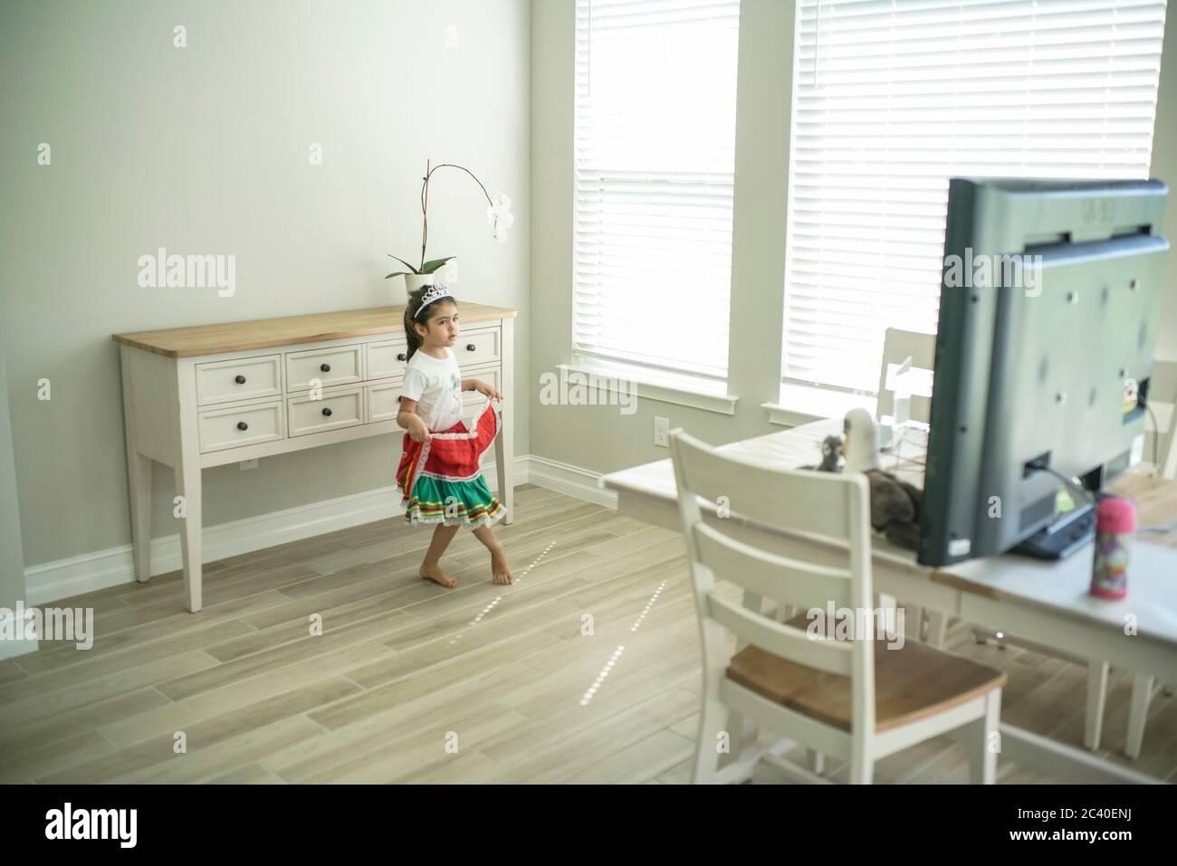Chica disfruta de una clase de baile en línea con un ordenador portátil conectado a una televisión en casa Foto de stock