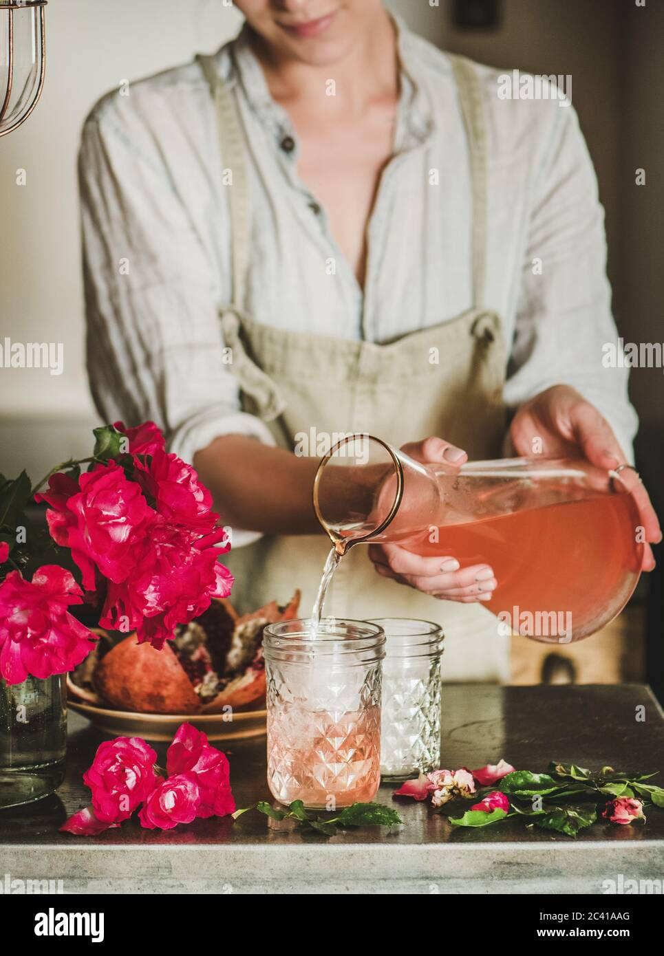 Mujer joven que vierte limonada de rosa a los vasos sobre el mostrador de la cocina Foto de stock