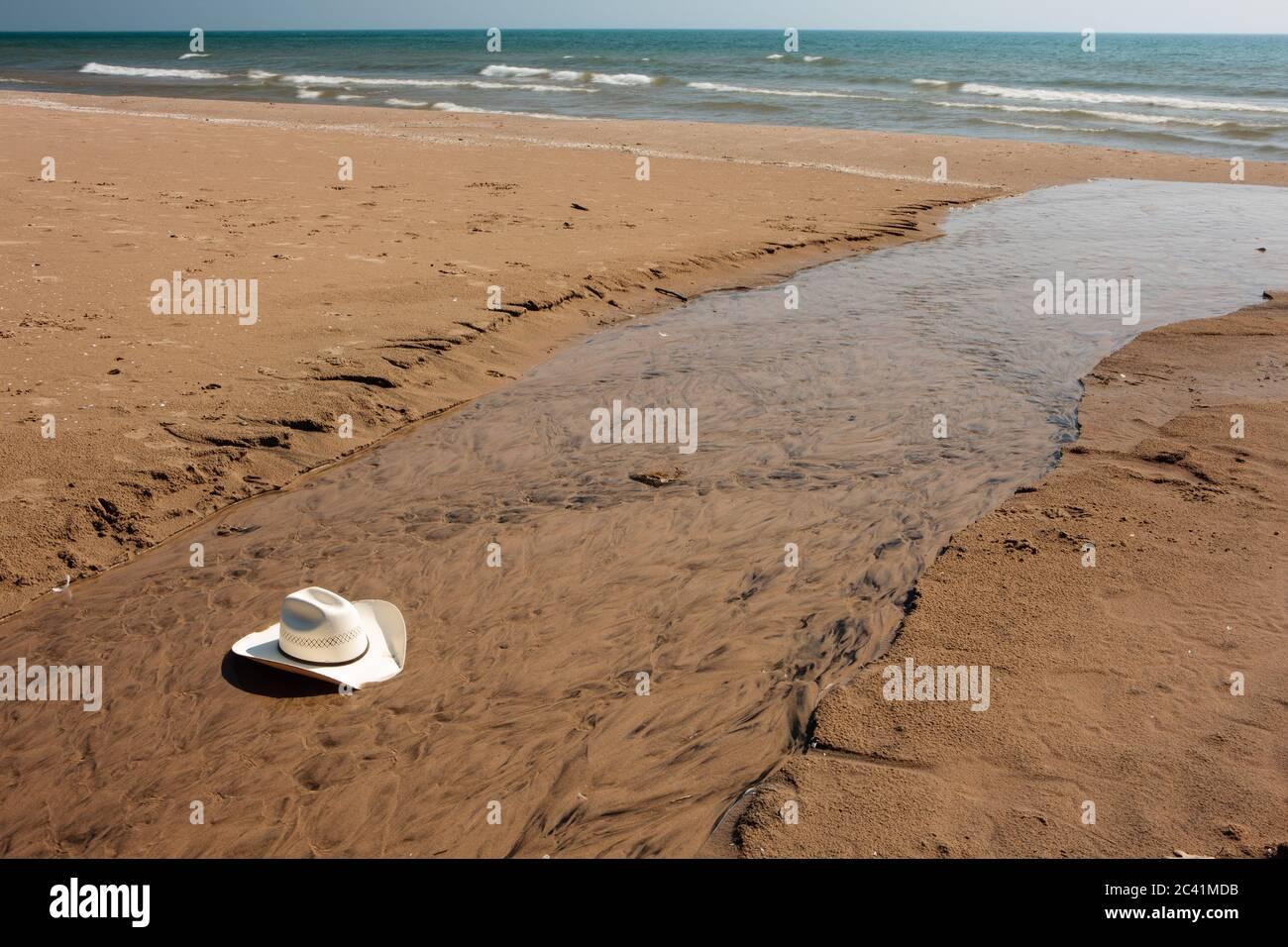 Un sombrero de vaquero, soplado fuera del fotógrafo durante los vientos a lo largo de la costa del Lago Michigan, es capturado después de rodar a lo largo de la playa por un shal Foto de stock