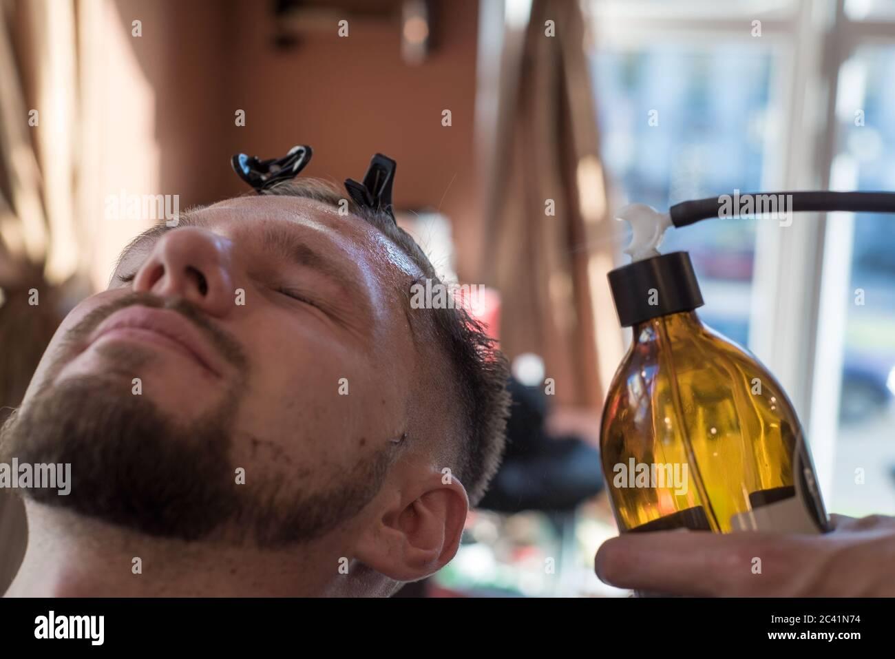 una peluquería rociando un bálsamo después de afeitarse la barba a un cliente de un joven barbudo de veinticinco años. A la peluquería Foto de stock