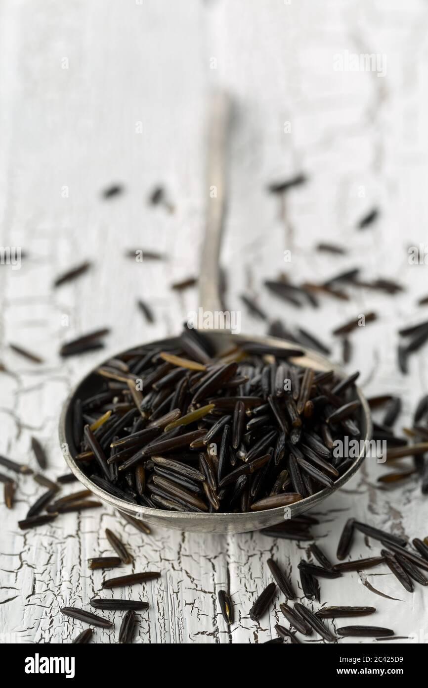 Montón de granos de arroz salvaje crudos, crudos y negros en cuchara de metal sobre fondo blanco de mesa rústica, enfoque selectivo Foto de stock