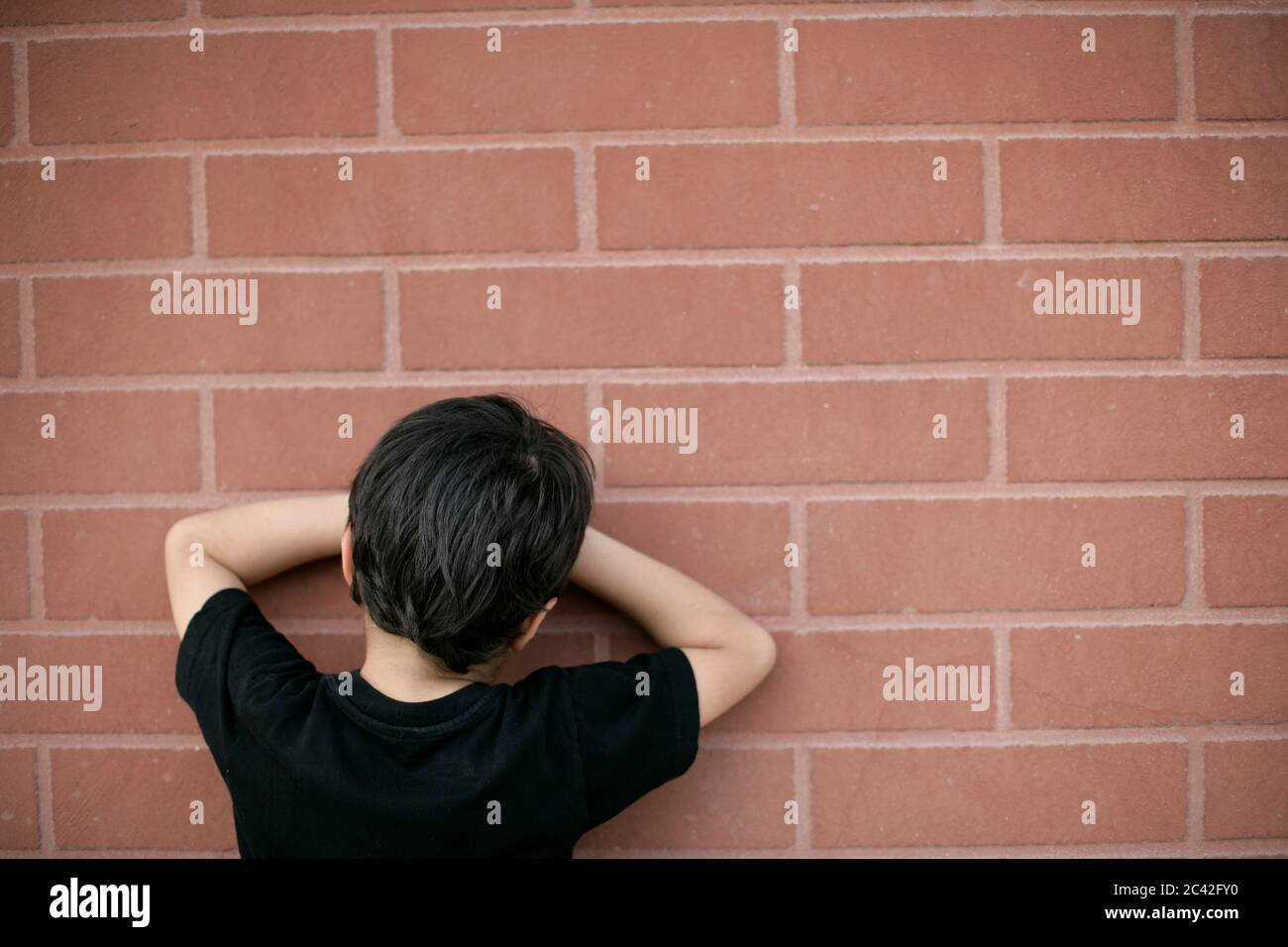 El niño cuenta con la pared para esconderse - la juventud - la infancia Foto de stock