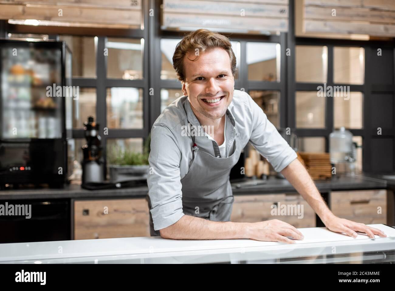 Retrato de un alegre vendedor en un delantal de pie detrás del mostrador de una pequeña tienda o cafetería. Concepto de pequeña empresa y trabajo en el campo de los servicios Foto de stock