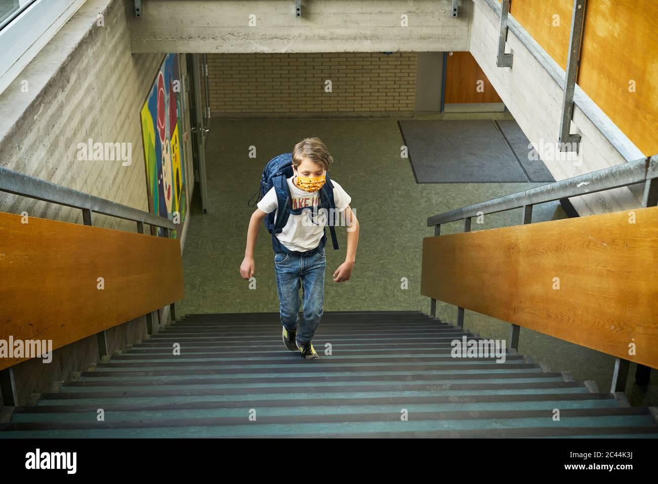 Niño usando máscara en la escuela subiendo las escaleras Foto de stock