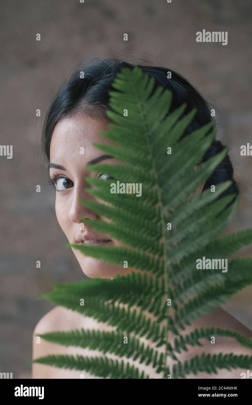 Hermosa mujer joven escondida detrás de las hojas de helecho Foto de stock