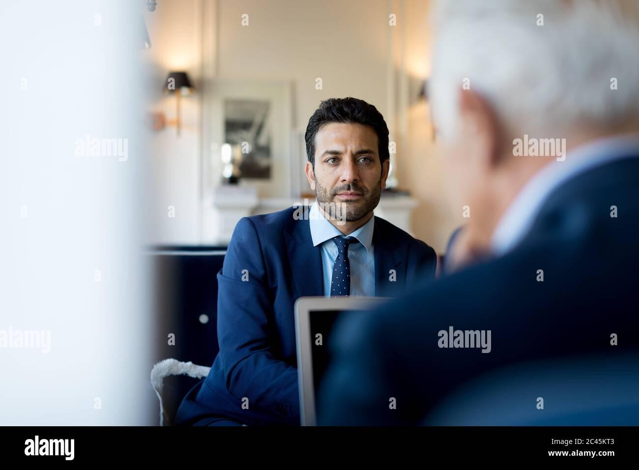 Dos hombres de negocios sentados en el interior, hablando. Foto de stock