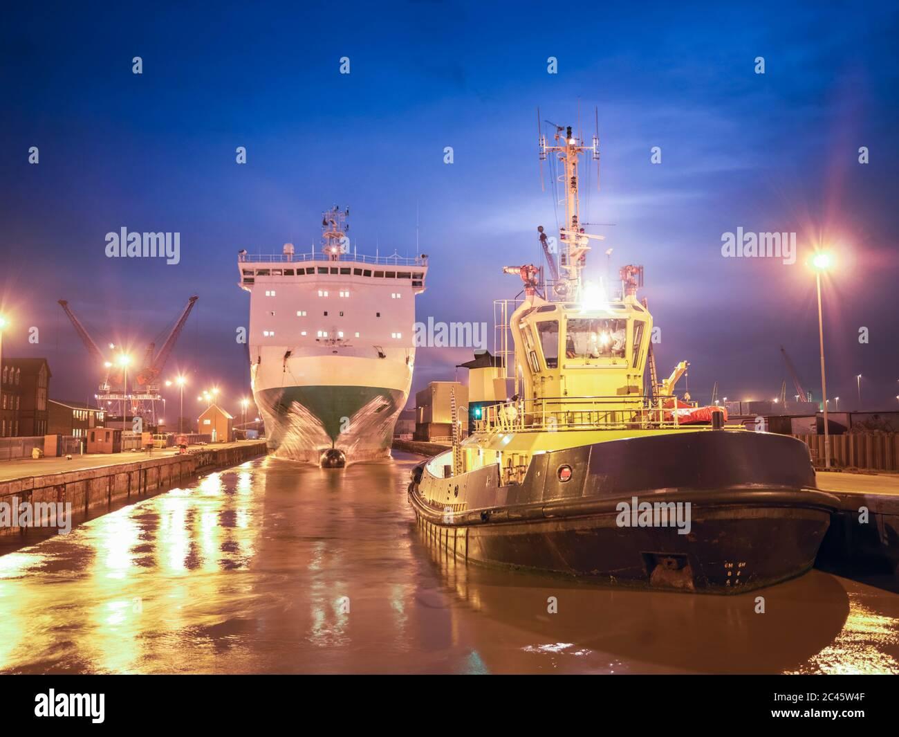 Remolca un bote esperando en el mar para remolcar el ferry desde el puerto al mar por la noche. Foto de stock