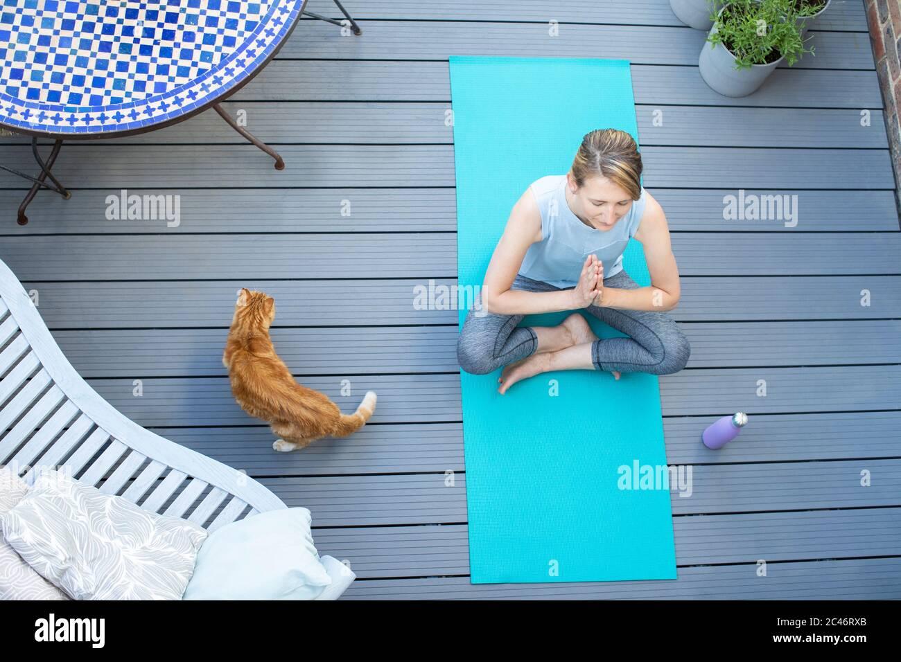 Vista superior de la mujer madura con gato de mascotas en casa meditando con yoga en cubierta Foto de stock