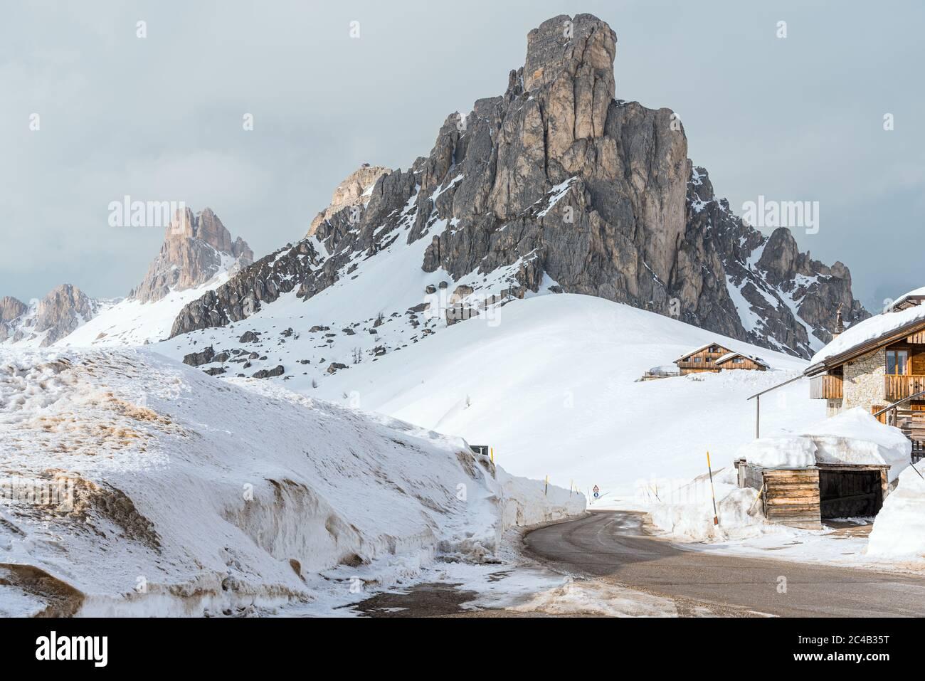 Camino vacío y sinuoso despejado de nieve en un paisaje de montaña de invierno en los Dolomitas en un día nublado Foto de stock