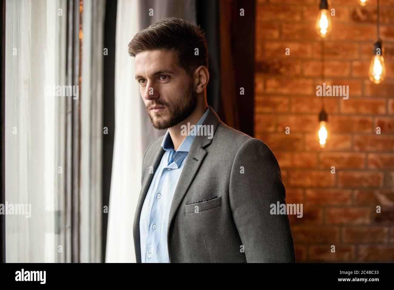 Hombre de negocios pensando en la oficina mirando a través de la ventana. Foto de stock