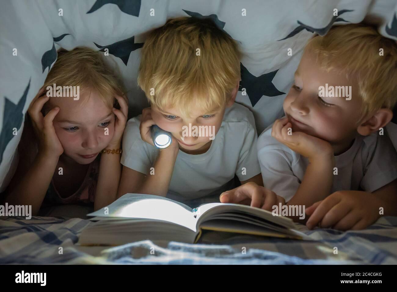 Tres niños pequeños están leyendo un libro con una linterna debajo de las cubiertas por la noche. Foto de stock