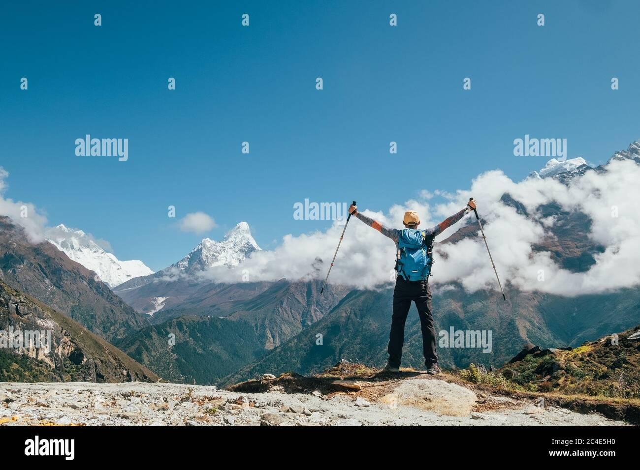 Imagen del concepto de vacaciones activas. Joven excursionista mochilero hombre elevándose brazos con bastones de trekking disfrutando de la montaña Thamserku 6608m durante la altitud Foto de stock