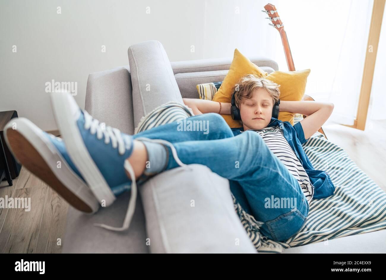 Un niño preadolescente durmiendo acostado en la sala de estar de la casa llena de luz solar en el sofá acogedor vestido con jeans y zapatillas de deporte informal escuchando música Foto de stock