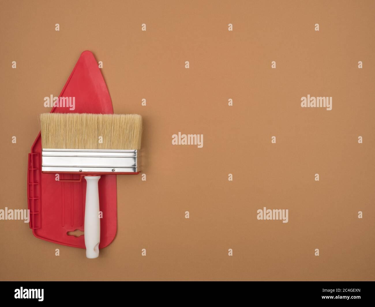 Espátula para alisar papel tapiz y un gran pincel de pintura. Fondo beige. Foto de stock