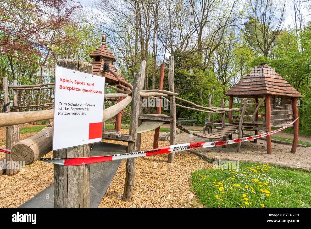 Parque cerrado con cinta de policía y señal de advertencia (texto en alemán: Patio cerrado) debido al virus de la Corona (Covid-19) Foto de stock