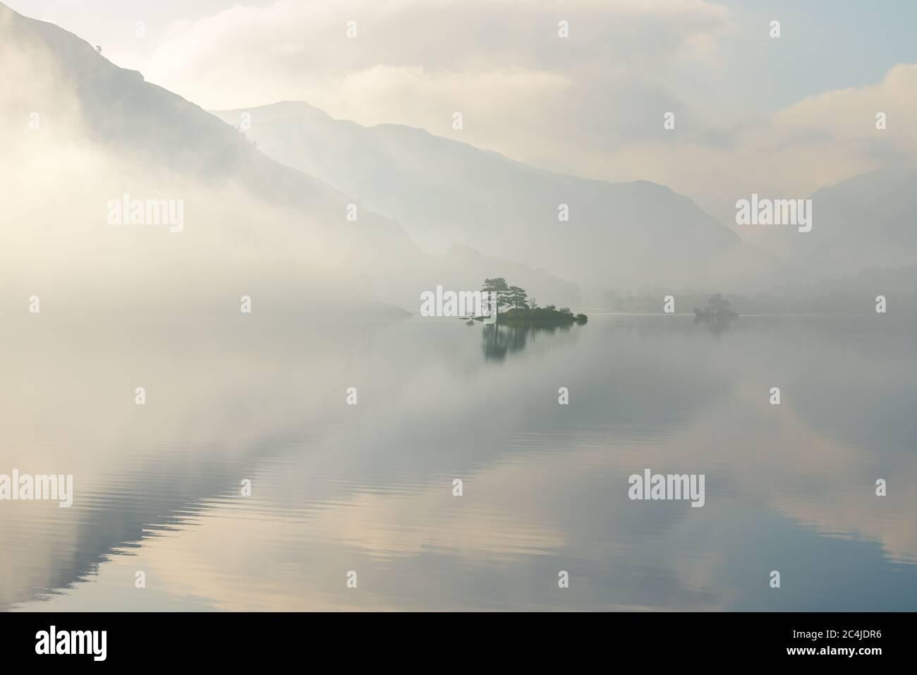 Isla aislada reflejada en UN tranquilo lago en UNA tranquila mañana de verano Misty. Lake District, Reino Unido. Foto de stock