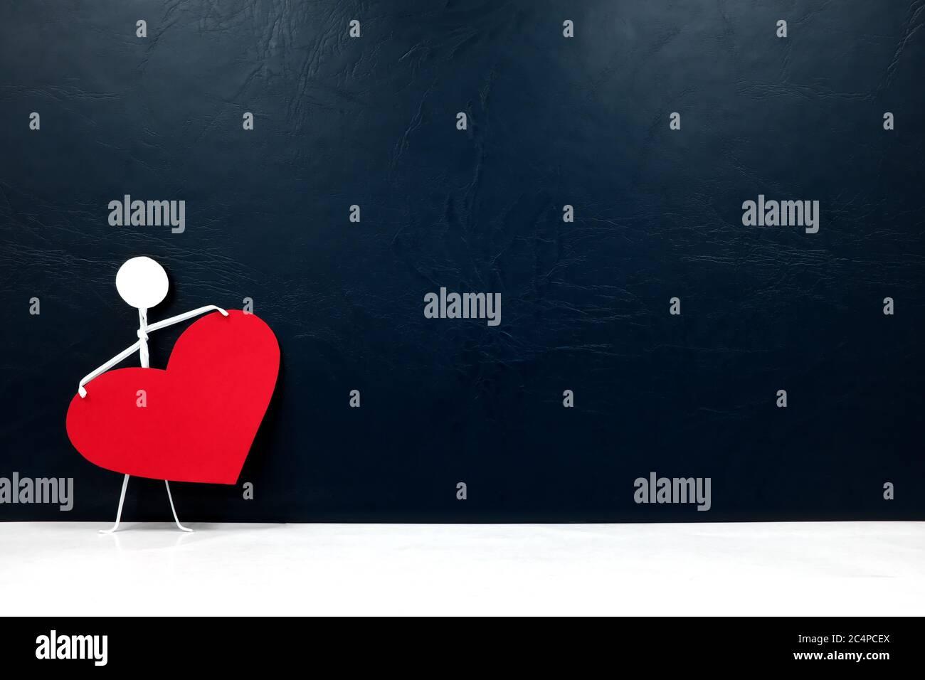 Figura de palo humano que sostiene un corazón rojo grande en fondo oscuro. Dar amor y solo valentines día de celebración concepto. Foto de stock