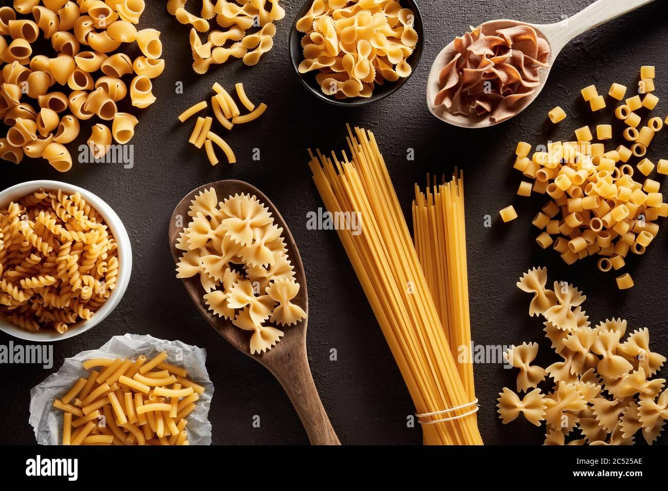 Montón de varias pastas crudas en diferentes tipos y formas sobre fondo marrón oscuro. Vista de gastos generales. Foto de stock