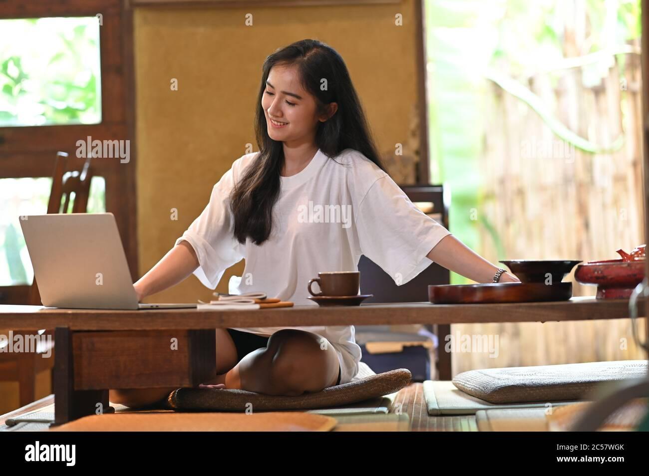Una mujer hermosa está estirando su brazo mientras trabaja con un ordenador portátil en la mesa de madera de piernas cortas. Foto de stock
