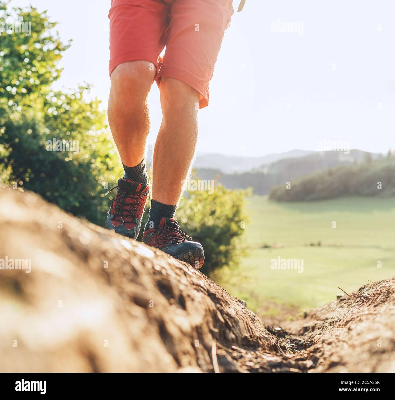 Close up imagen mochilero pies en botas de trekking en camino sucio montaña en verano día soleado. Foto de stock