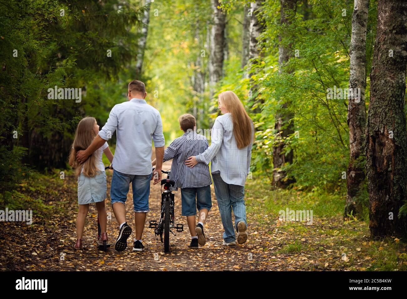 Feliz familia al aire libre sonriendo en un bosque de verano Foto de stock