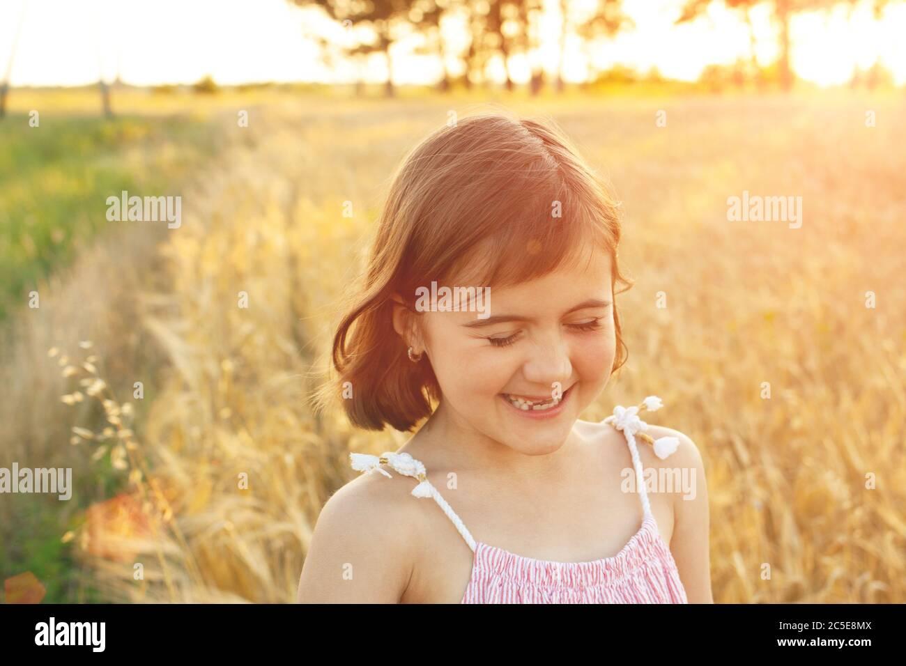 Chica divertida se ríe en un paseo por el campo al atardecer. El concepto de la infancia real, detox digital, vacaciones de verano, la felicidad. Foto de stock