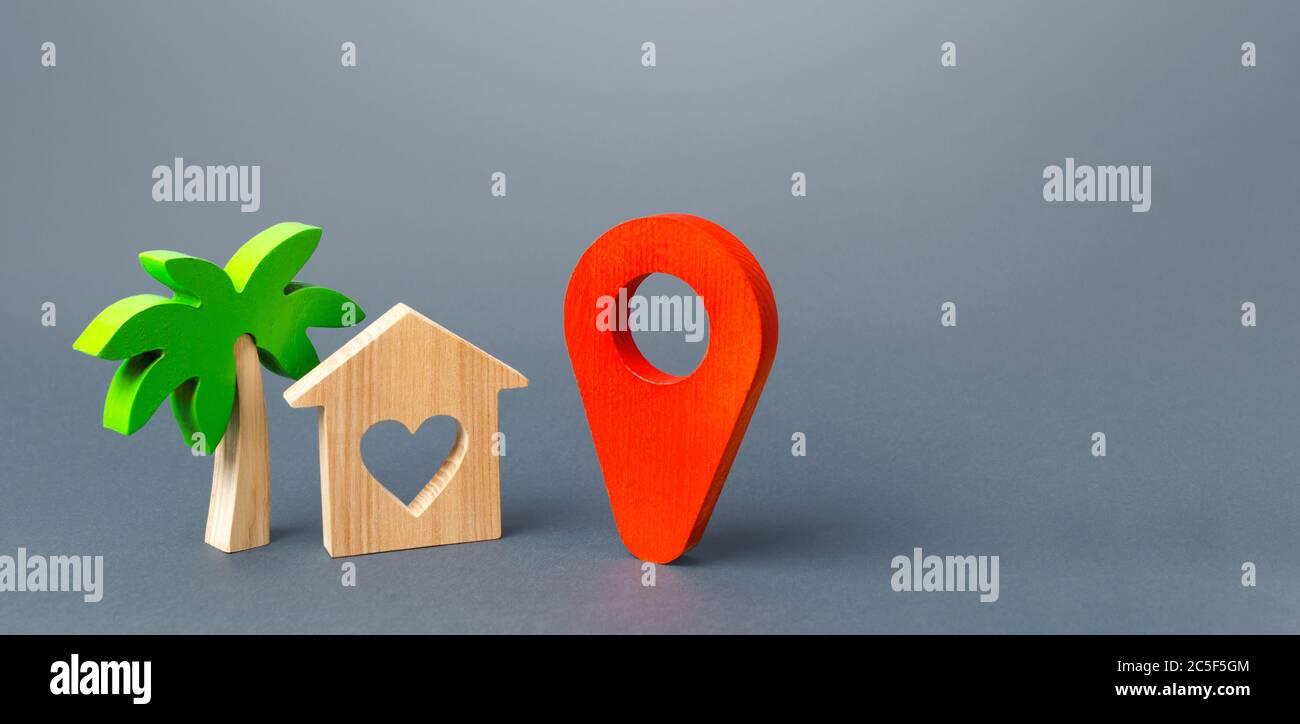 Casa con un corazón y un puntero de navegación rojo. Elegir un lugar para un viaje romántico. Una guía turística en el mundo post-pandemia. Nuevas reglas para t Foto de stock