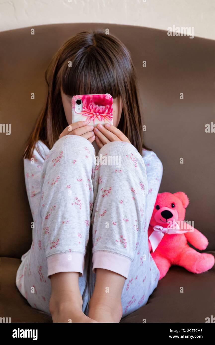 Niña de ocho años jugando en un teléfono inteligente Foto de stock