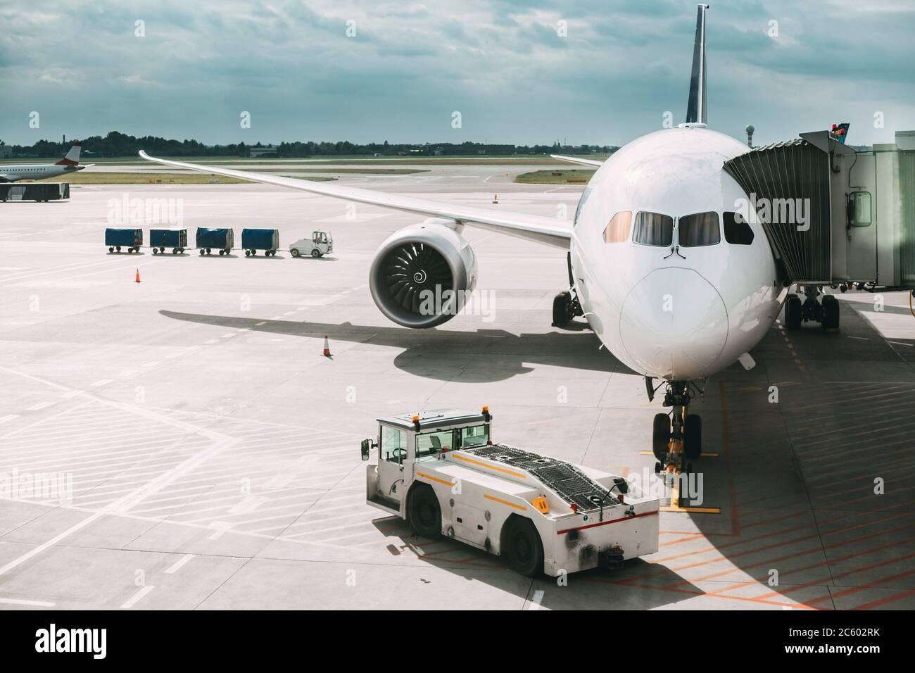 Plano de aviones de pasajeros de embarque en la terminal del aeropuerto. Tractor de remolque de aeronaves y el espanto carretilla cerca del avión. Foto de stock