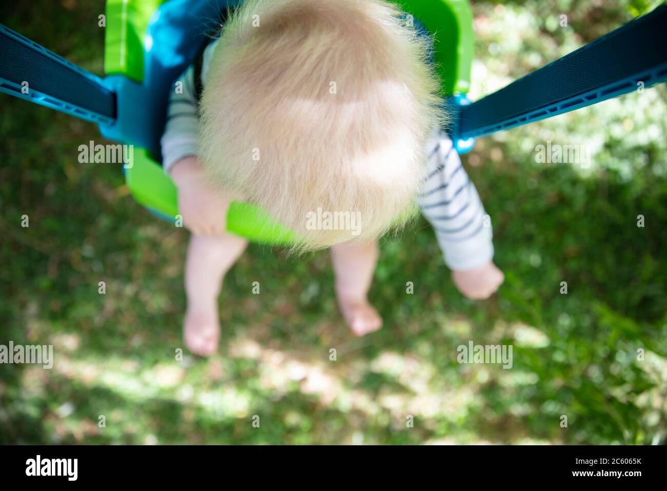 Un niño pequeño que se divierte jugando en un columpio bajo un árbol en un jardín Foto de stock