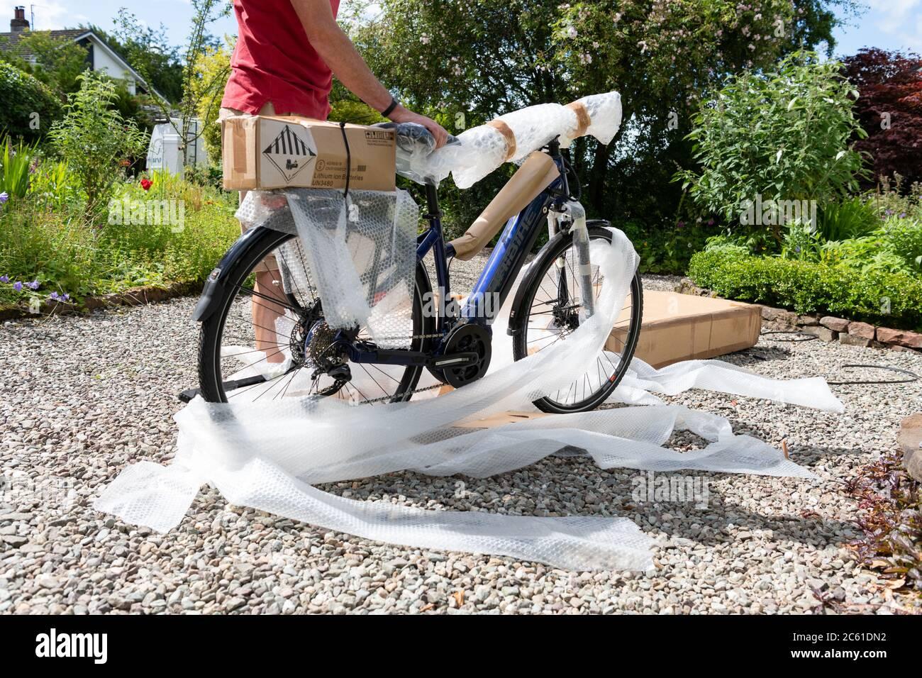 Entrega en casa de bicicleta eléctrica ebike pedido en línea durante el cierre coronavirus - bicicleta sacada de la caja de bicicletas y desenvolver envoltura de burbujas - Reino Unido Foto de stock