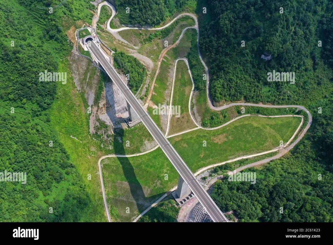 Liupanshui. 6 de julio de 2020. Foto aérea tomada el 6 de julio de 2020 muestra un puente ferroviario a lo largo del ferrocarril Anshun-Liupanshui en la provincia de Guizhou, al suroeste de China. El ferrocarril interurbano Anshun-Liupanshui, con una velocidad de 250 km por hora, está en preparación para su apertura. El ferrocarril acortará el tiempo de viaje entre Guiyang y Liupanshui de las actuales 3.5 horas a aproximadamente 1 hora, y la ciudad de Liupanshui estará completamente conectada con la red nacional de trenes de alta velocidad. Crédito: Liu Xu/Xinhua/Alamy Live News Foto de stock
