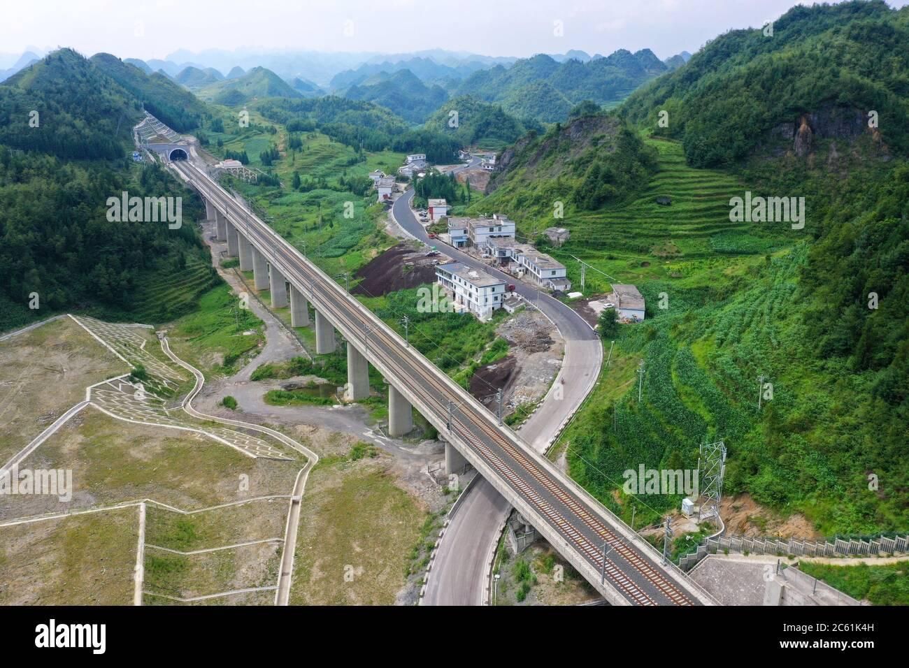 Liupanshui. 6 de julio de 2020. Foto aérea tomada el 6 de julio de 2020 muestra el ferrocarril Anshun-Liupanshui en la provincia de Guizhou, al suroeste de China. El ferrocarril interurbano Anshun-Liupanshui, con una velocidad de 250 km por hora, está en preparación para su apertura. El ferrocarril acortará el tiempo de viaje entre Guiyang y Liupanshui de las actuales 3.5 horas a aproximadamente 1 hora, y la ciudad de Liupanshui estará completamente conectada con la red nacional de trenes de alta velocidad. Crédito: Liu Xu/Xinhua/Alamy Live News Foto de stock