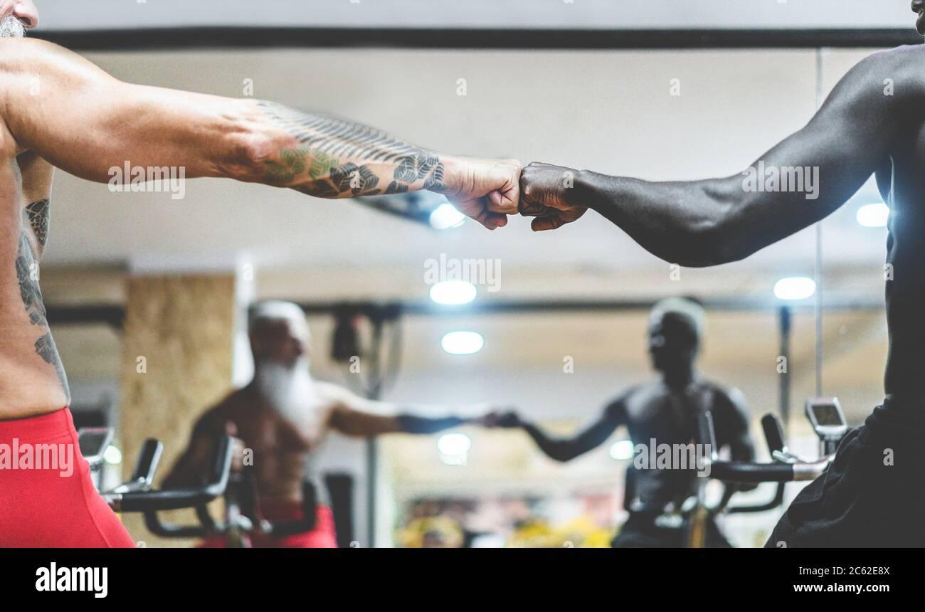 Gente de diferentes generaciones y etnias haciendo ejercicio en cardio ciclette dentro del gimnasio club - Fitness, spinning, no racismo y deporte con Foto de stock